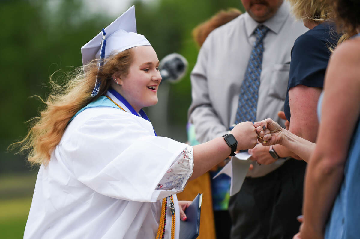 Coleman High School Class of 2021 valedictorian Alexis Smith gives a fist bump to a school administrator during a commencement ceremony Sunday, May 23, 2021 at the school in Coleman. (Adam Ferman/for the Daily News)