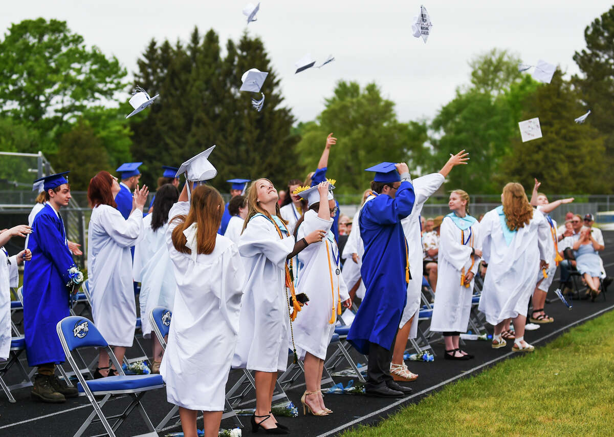 The Coleman High School Class of 2021 tosses their caps during a commencement ceremony Sunday, May 23, 2021 at the school in Coleman. (Adam Ferman/for the Daily News)