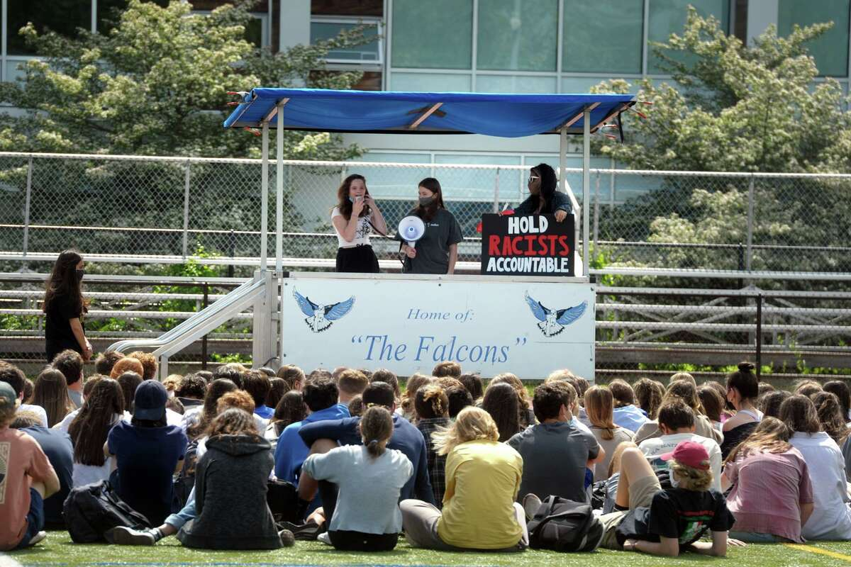 Fairfield Ludlowe High School students listen to some of their classmate speak during an organized walk out in Fairfield, Conn. May 24, 2021. Students at Ludlowe and across town at Fairfield Warde High School held walk outs Monday morning to protest recent racist incidents.