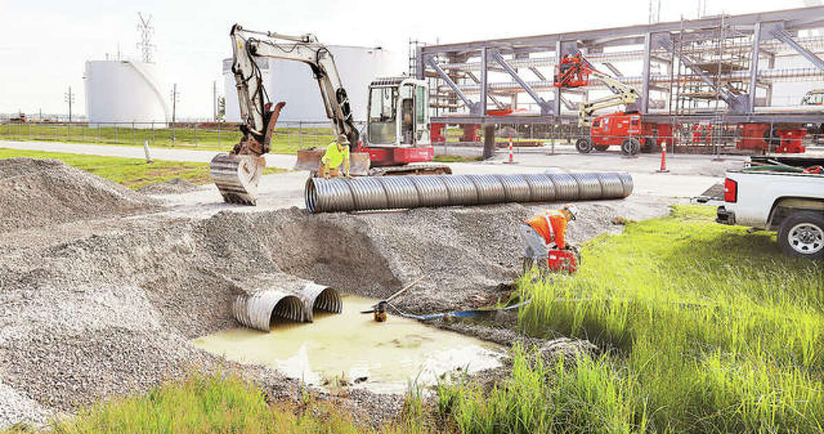 Workers on Monday were seen constructing two packed rock roads to bridge the ditch between State Aid Road and Illinois 3 in Hartford. Multi-wheeled supports from Mammoet Heavy Transport will use the makeshift rock roads to move the pipeline bridge into place.