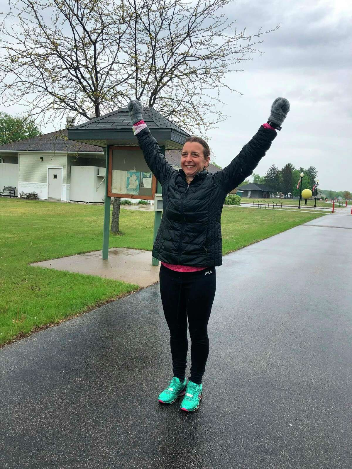 Sarah Holsinger raises her arms in celebrationafter running 81 miles from Cadillac toColeman. (Photo provided)
