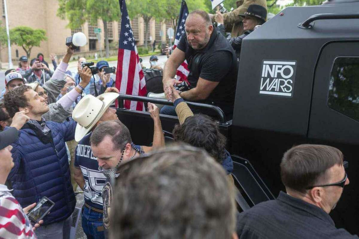 Alex Jones greets supports as he exits a protest at the Texas Capitol in Austin looking to end to the coronavirus shutdowns, Saturday, April 19, 2020.