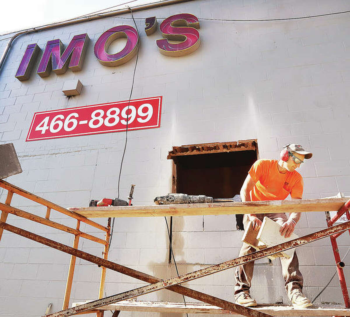 Workers on Monday cut a hole in the north side of the Godfrey Imo's Restaurant at 2704 Godfrey Road for a drive-up window. The restaurant, which was severely damaged in an October fire, previously did not have a drive-up window. No date has been set for the restaurant's reopening.