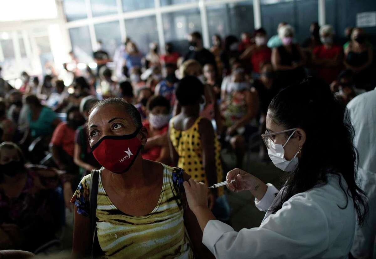 In this April 28, 2021 file photo, a healthcare worker injects a woman with a dose of the Sinovac COVID-19 vaccine in Sao Joao de Meriti, Rio de Janeiro state, Brazil. Most nations are short of vaccines, but Brazil's government in particular neglected to chase deals, and just 8.5% of the population is fully vaccinated as of late May 2021. (AP Photo/Silvia Izquierdo, File)