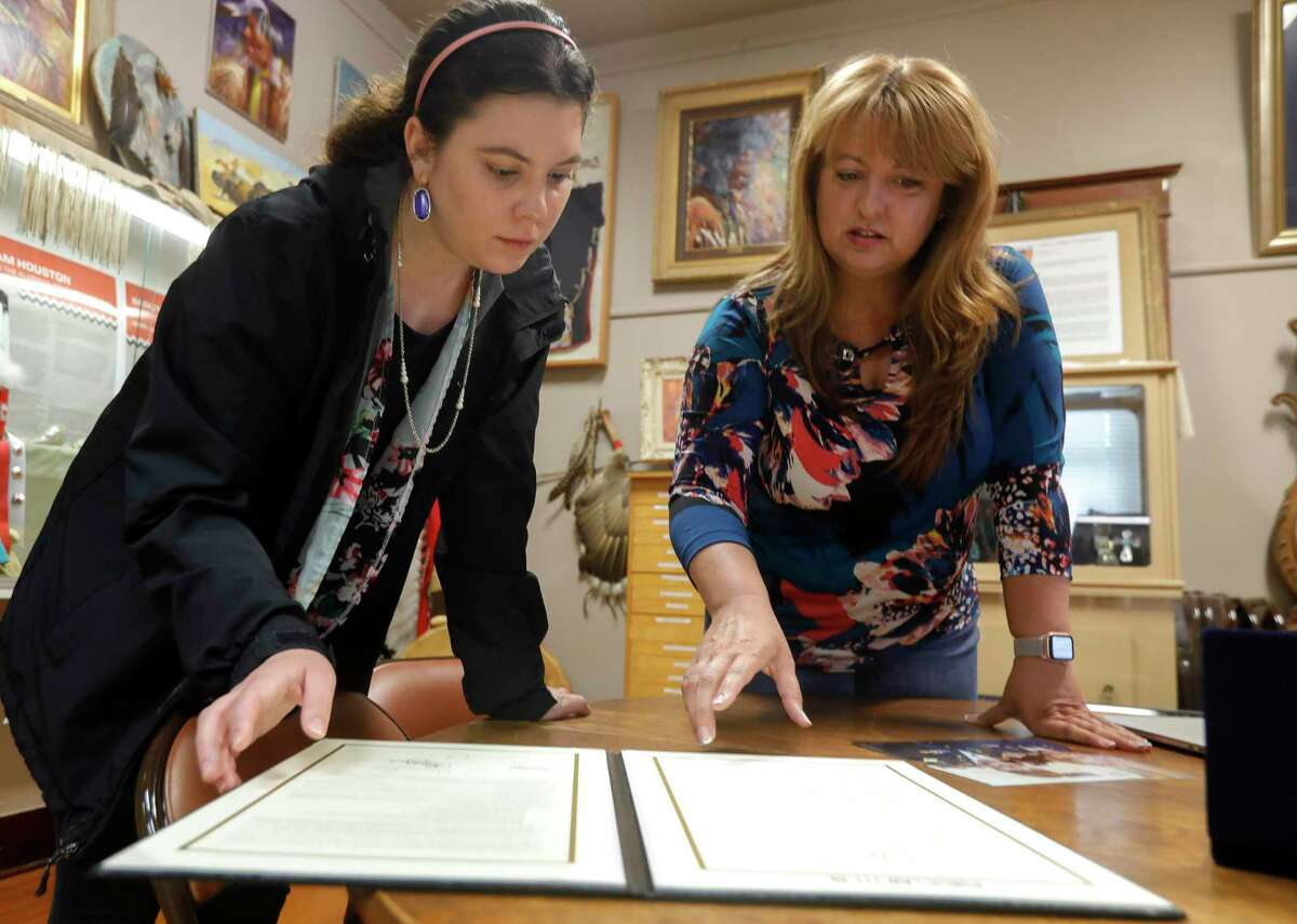 Roxi Anderson, right, shows memorabilia from the Women Airforce Service Pilots celebration she helped plan in 2010 to Catherine Pool, Friday, May 21, 2021, in Conroe. Anderson helped plan the celebration as part of former Senator Kay Bailey Hutchinson's staff. WASP was a Air Force program that tasked some 1,100 civilian women with noncombat military flight duties during World War II, making them the first women to fly U.S. military aircraft. The Heritage Museum of Montgomery County will dedicate a WASP monument on Memorial Day.