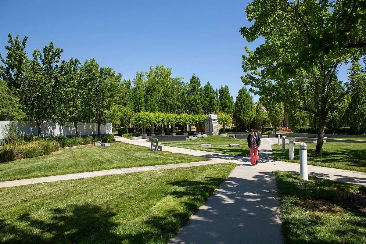 A woman walks through the Civic Center campus in Livermore, Calif. on Wednesday, May 19, 2021.
