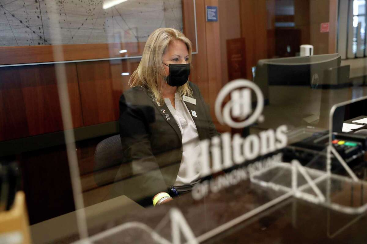 Nora Johnson works at the front desk as Hilton Union Square reopens for business.