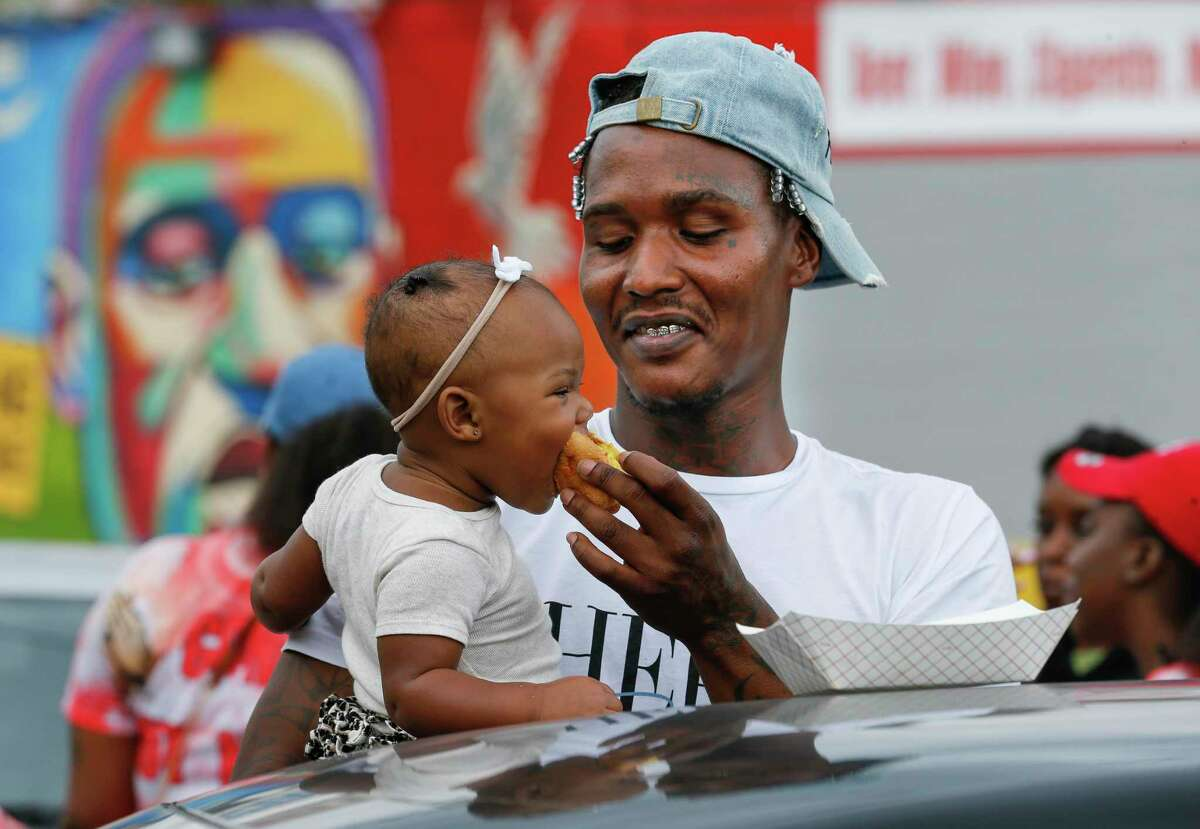 Chris Hutchins feeds her 11-month-old daughter Perfect, during a block party celebrating George Floyd's 47th birthday Saturday, Oct. 17, 2020, in Third Ward, Houston. Floyd, a former Houston resident, was killed by a Minnesota Police officer earlier this year, leding to nation-wide protests.