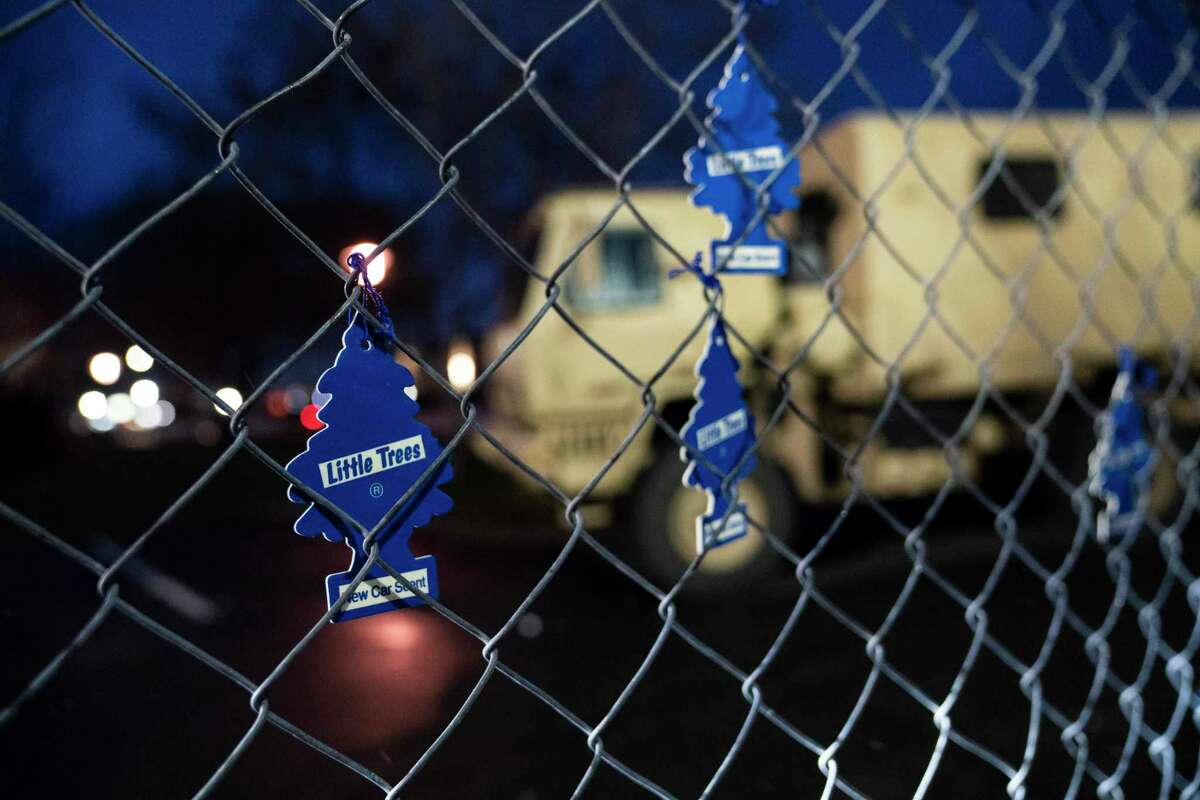 Demonstrators hang car air fresheners from a perimeter fence outside the Brooklyn Center, Minnesota, Police Department to protest the shooting death of Daunte Wright on April 11, 2021.
