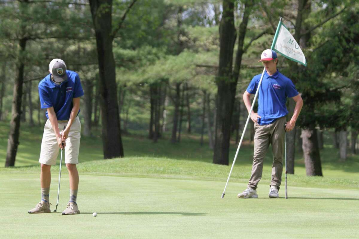 Manistee's Henry Hybza putts as teammate Blake Johnson looks on Monday at Manistee National Golf & Resort. (Dylan Savela/News Advocate)