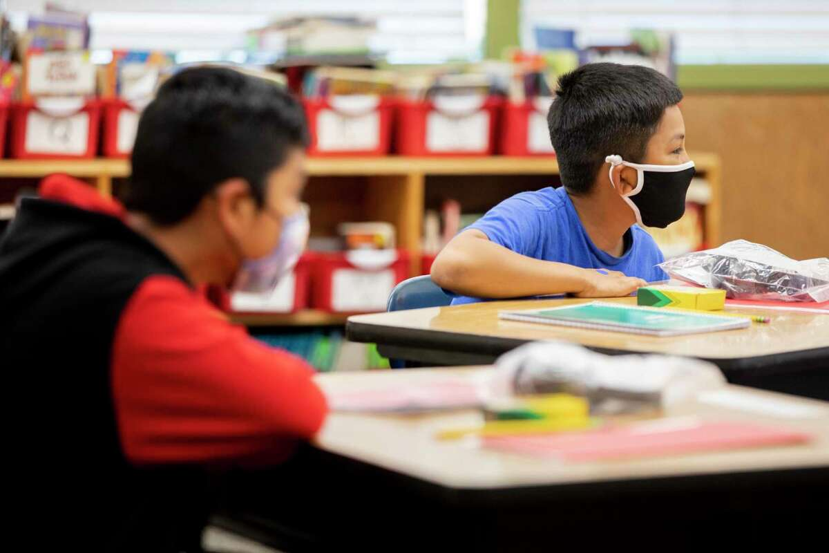 Fifth grade students wear masks while seated socially distanced from others in their desks at Garfield Elementary School in Oakland, Calif. Monday, April 19, 2021 during the first day of partial school-wide, in-person learning.