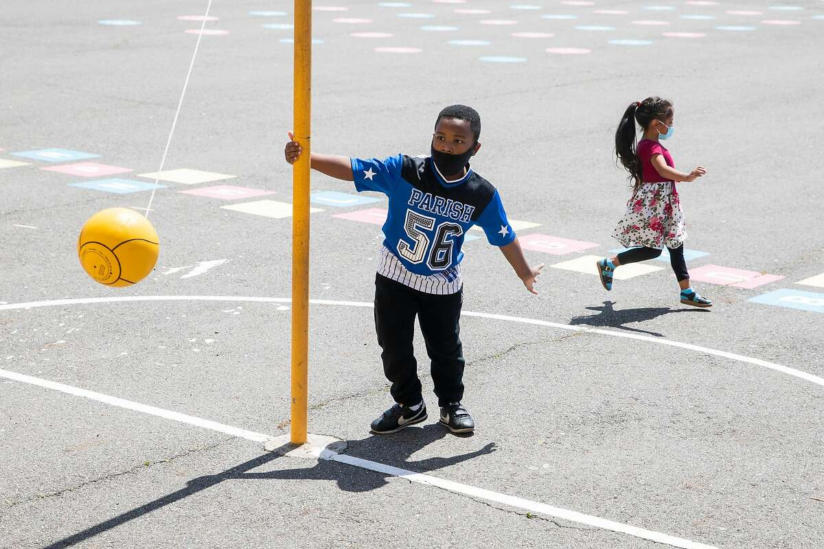 Second-graders wearing masks play during recess April 19 at Oakland's Garfield Elementary School.