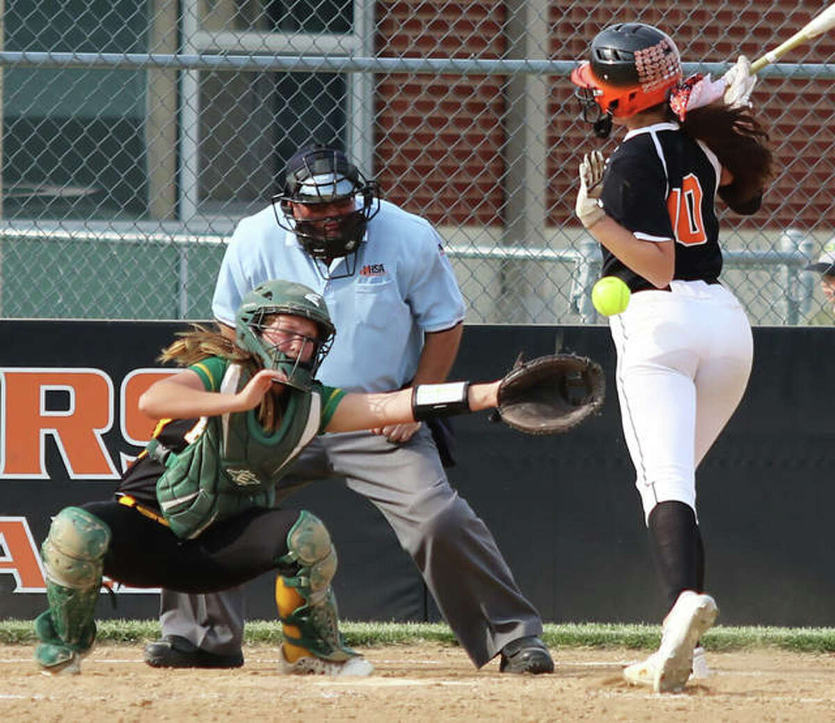 Gillespie's Keaton Link (right) can't avoid getting hit in the back by a pitch in the sixth inning while Southwestern catcher Abby McDonald reaches for the pitch that won't reach her glove Monday in a SCC softball game in Gillespie.