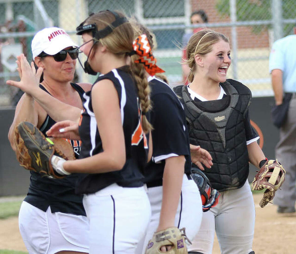 Gillespie catcher Hannah Barrett (right) waits for pitcher Sydney Bires to join the celebration while Miners coach Michelle Smith welcomes players off the field after a 4-1 win over Southwestern on Monday in Gillespie.