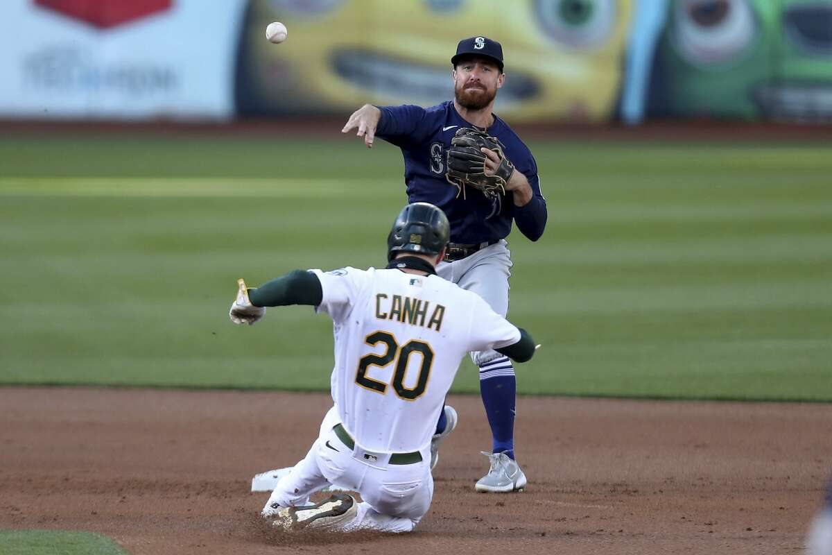 Seattle Mariners' Donovan Walton, top, throws to first as Oakland Athletics' Mark Canha slides into second on a double play hit into by Chad Pinder during the second inning of a baseball game in Oakland, Calif., Monday, May 24, 2021. (AP Photo/Jed Jacobsohn)