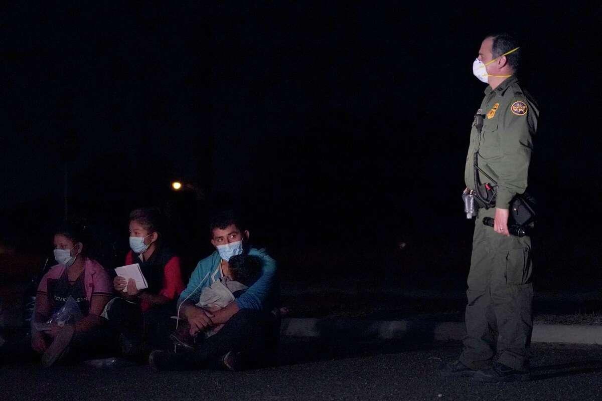 En esta imagen del 24 de marzo de 2021, un inmigrante, al centro, carga a un niño mientras mira a un agente de la Oficina de Aduanas y Protección Fronteriza en una zona de detención después de cruzar la frontera entre México y Estados Unidos, en Roma, Texas.
