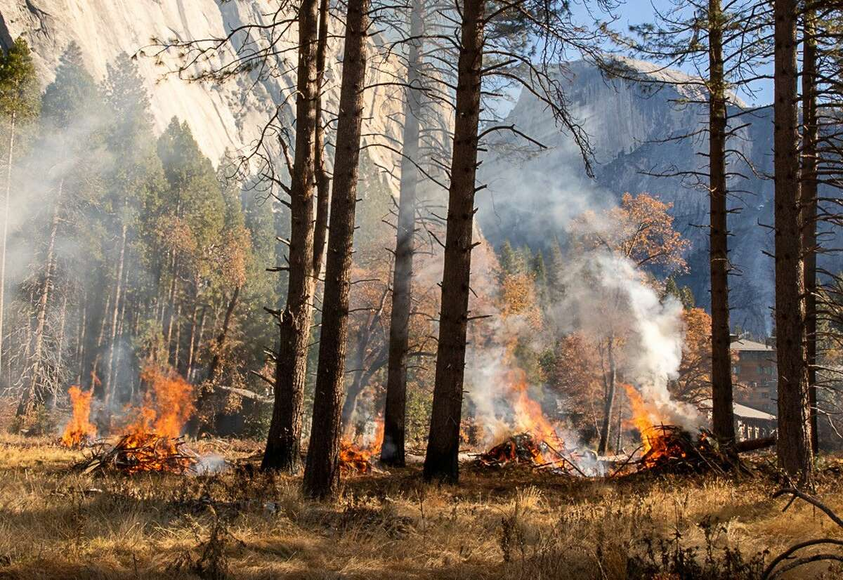 Half Dome is barely visible through the smoke from some small burn piles ignited in Ahwahnee Meadow in January 2021.