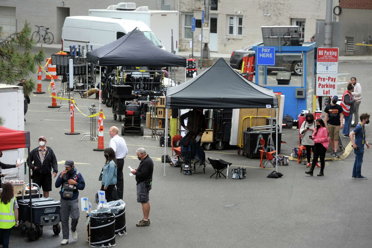 """Members of a film crew gather on Mechanic St. near the set where scenes for """"The Good Nurse"""" are being filmed in Norwalk, Conn. May 24, 2021."""