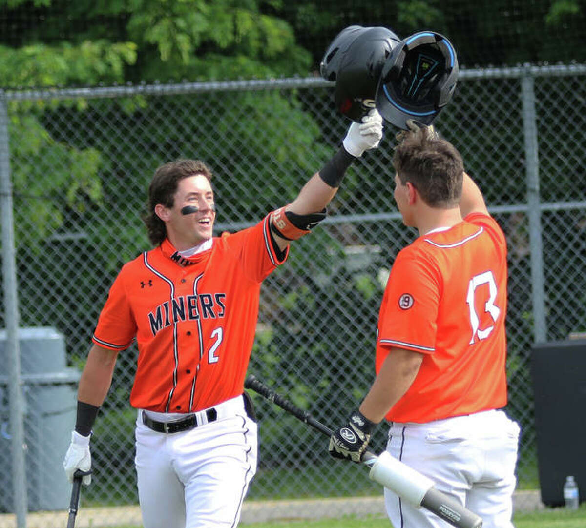 Gillespie's Cameron Hailstone (left) gets a congratulatory helmet tap from teammate Gavin Griffith after Hailstone's first of two home runs in the Miners' win over Southwestern on Monday in Gillespie.