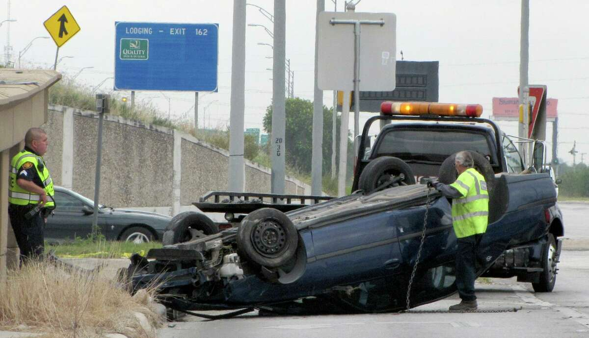A tow truck driver flips over a vehicle that rolled off Interstate 35 at Rittiman Road about 8:30 a.m. on Friday, November 23, 2012. Police suspect the crash was caused by an intoxicated wrong-way driver.