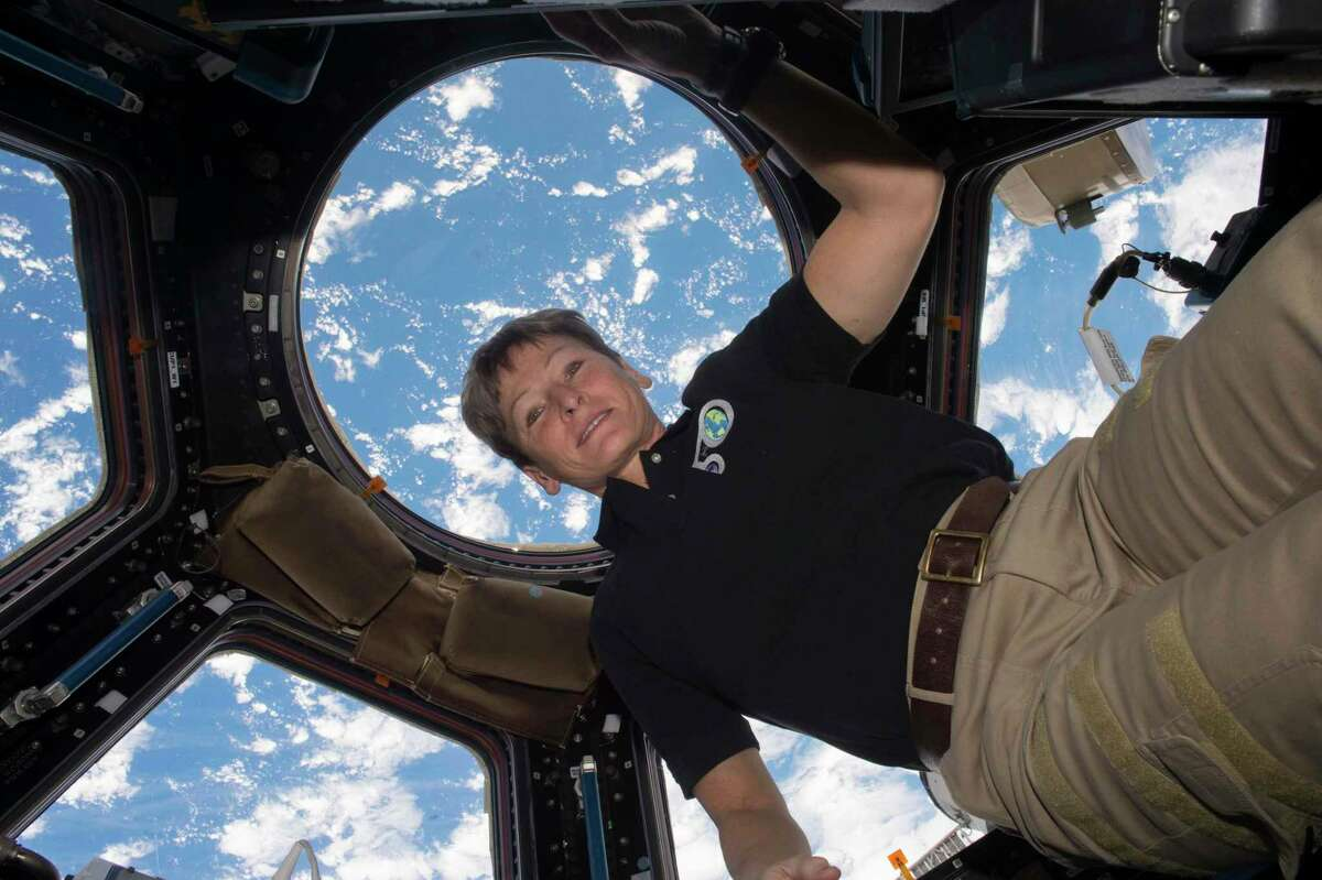 In this Dec. 3, 2016 photo made available by NASA, astronaut Peggy Whitson poses for a photo in the cupola of the International Space Station, with the Earth in the background. (NASA via AP)