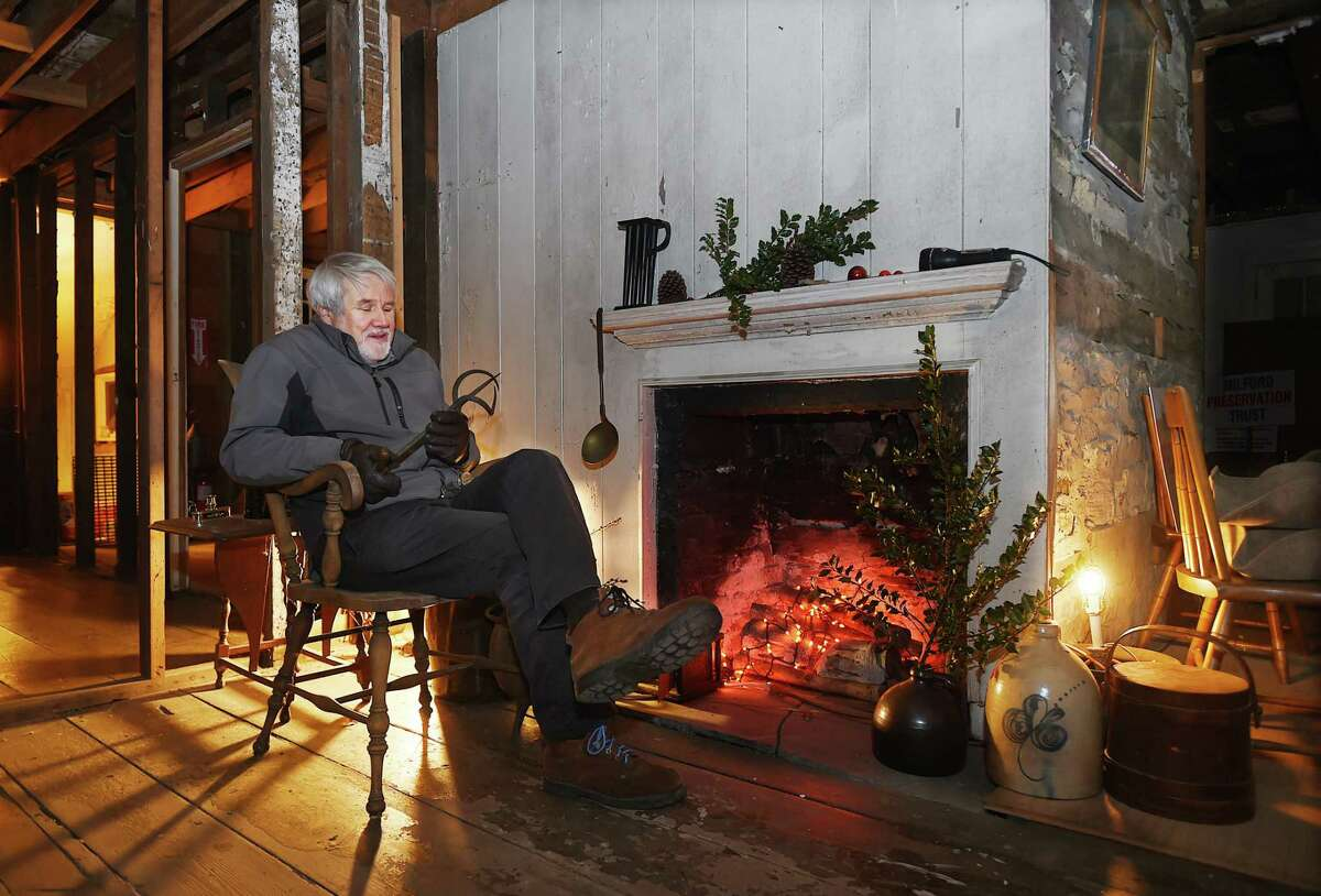 Tim Chaucer, a member of the Milford Preservation Trust Board of Directors examines a fruit auger or more popularly known as a sugar devil, Thursday, Dec. 21, 2017, at the Minuteman House in Milford.