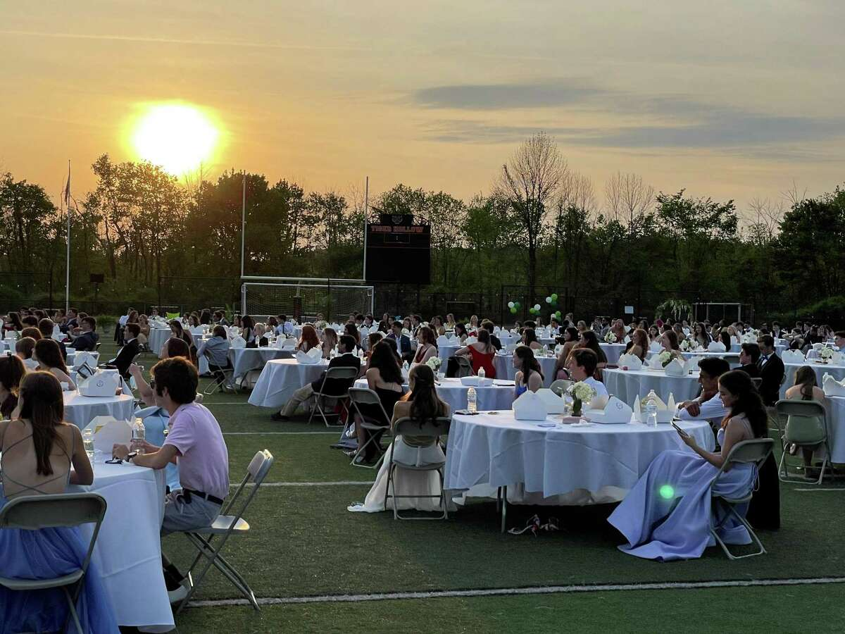 Ridgefield High School seniors sat at socially-distanced tables on the football field at Tiger Hollow stadium on Friday, May 21.