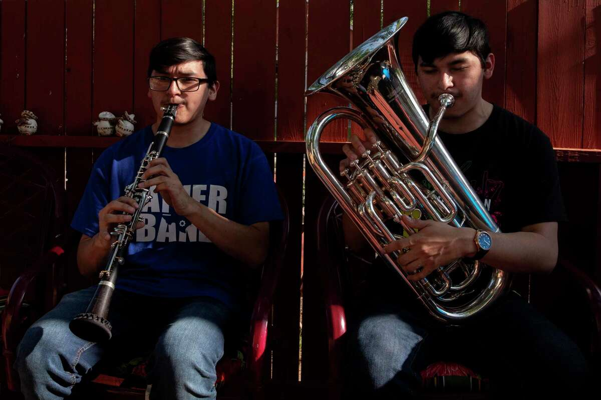 Fabien and Damien Chavez play the clarinet and euphonium, respectively, in their backyard. The twins are graduating from Lanier High School as valedictorian and salutatorian after making all-region and all area band. Fabien also made all-state band.