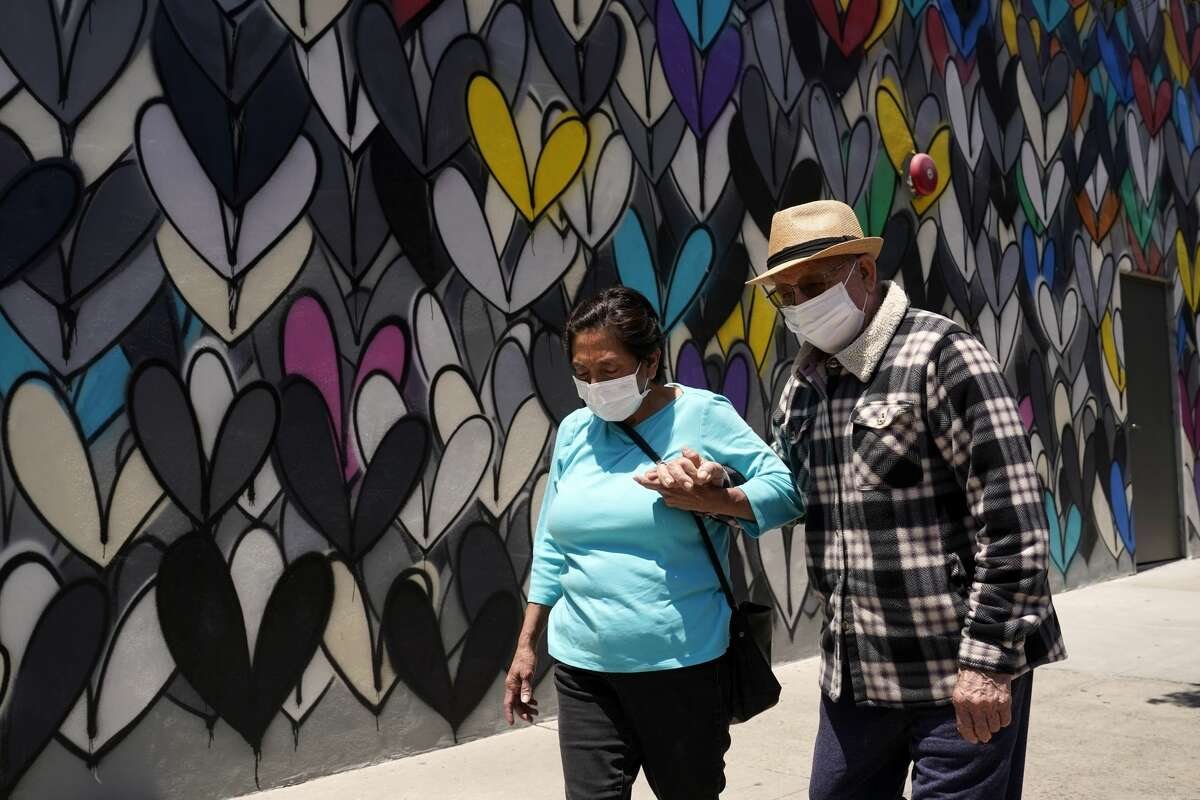 A couple wear face masks and hold hands as they walk past a mural amid the COVID-19 pandemic Tuesday, May 18, 2021, in Burbank, Calif.