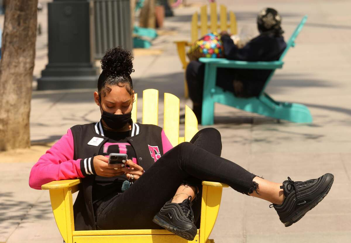 Imani Ross, 24, wearing a mask against COVID-19, takes a break from work at T Mobile on the Third Street Promenade a day after the CDC relaxed the use of wearing masks in Santa Monica on May 14, 2021.