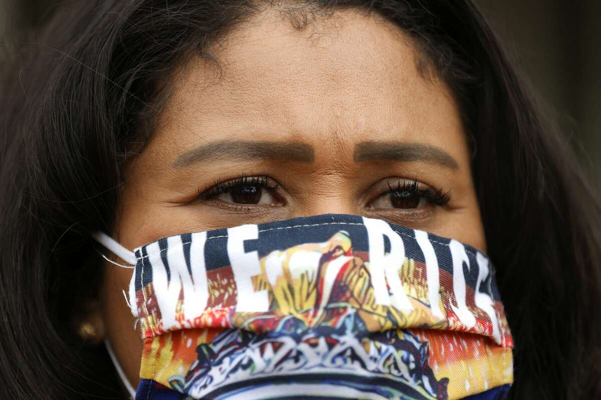 """San Francisco Mayor London Breed wears a face mask that says """"We Rise"""" during a news conference outside of Zuckerberg San Francisco General Hospital with essential workers to mark the one year anniversary of the COVID-19 lockdown on March 17, 2021 in San Francisco, California."""