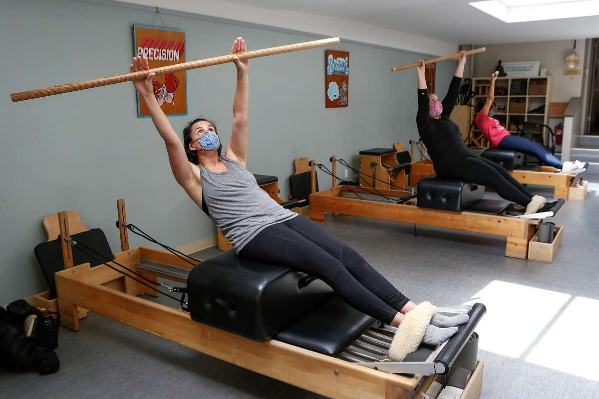 Danielle Kellar (left) and Penelope Robinson (center right) follow along with instructor Myra Phipps (left) at EHS Pilates Studio on Tuesday, May 25, 2021 in San Francisco, Calif.