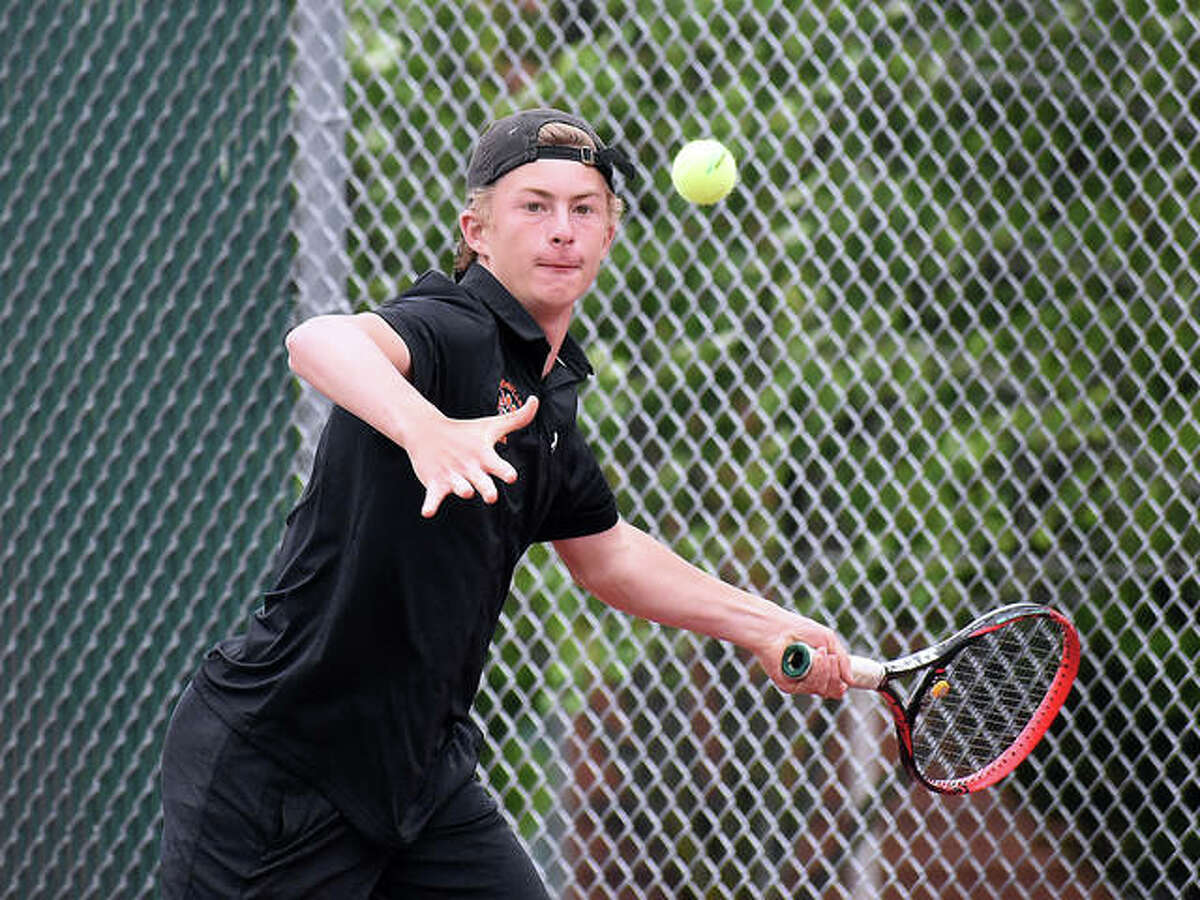 Edwardsville's Colton Hulme hits a return shot during his doubles match against O'Fallon earlier this season at the EHS Tennis Center.