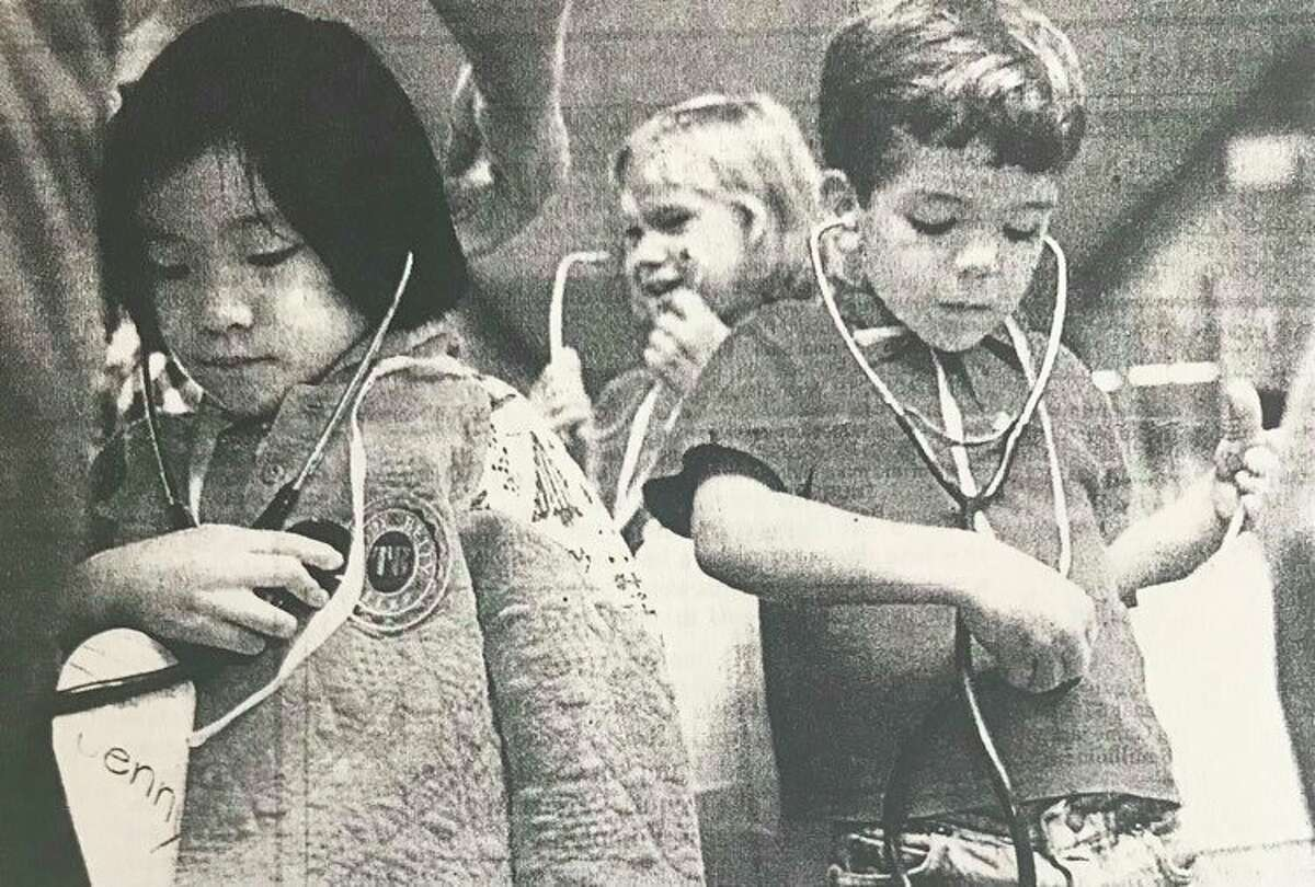 Jenny Huang, left, listens to her heart beat while Seamus Gallagher checks out his stomach. In back is Heidi Thomson. The Siebert Elementary School kindergartners were learning about emergency procedures at MidMichigan Medical Center. October 1996