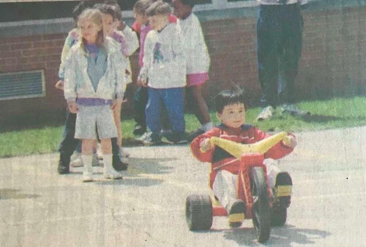 Anthony Ho, anak TK Sekolah Dasar Siebert, mengambil gilirannya dengan Relay Roda Besar selama acara masak tahunan sekolah dan hari lapangan. Mei 1996