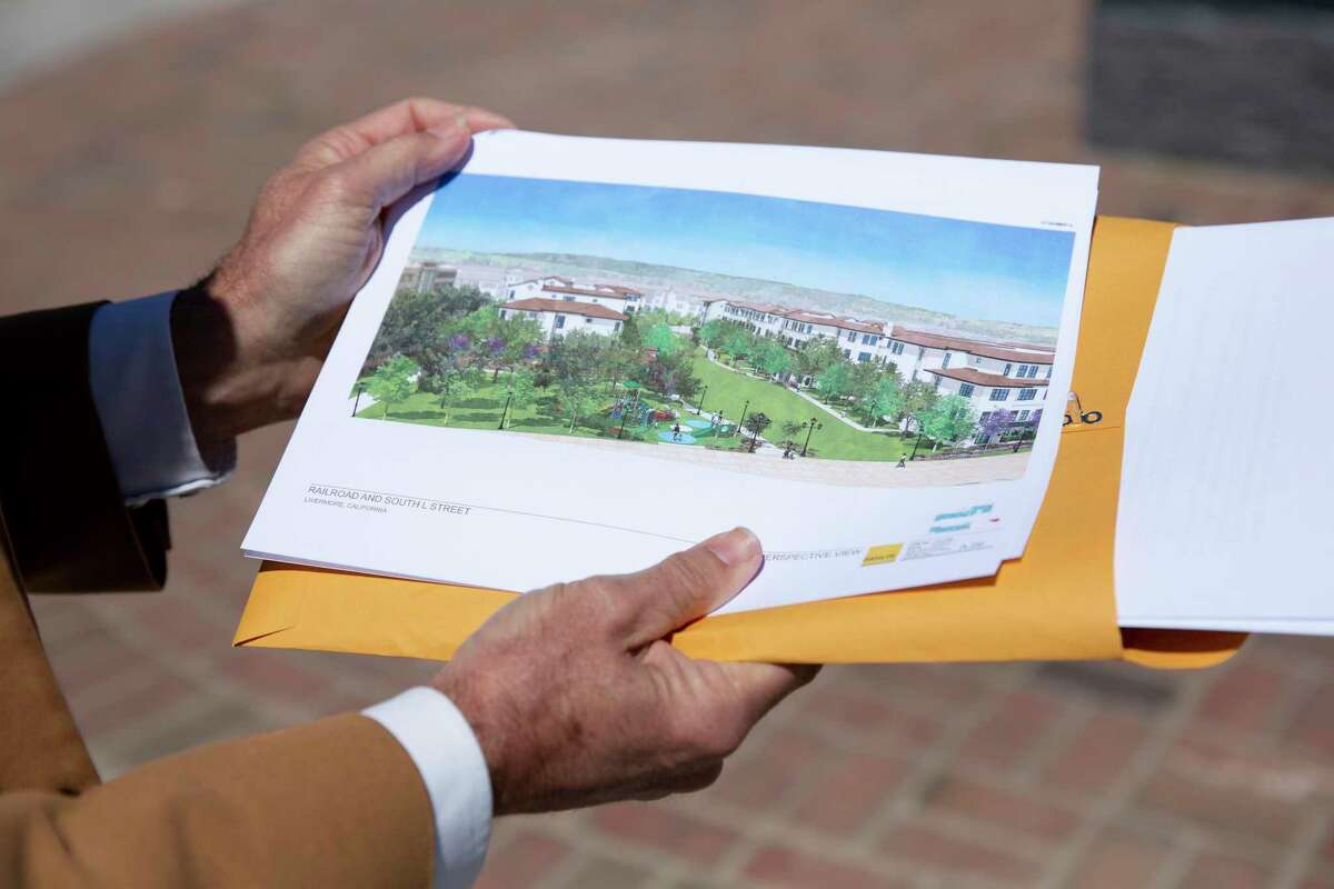 John Marchand, a former mayor of Livermore, holds a print of the new affordable housing project that is suppose to be built in conjunction with Stockmen's Park in Livermore, Calif. on Wednesday, May 19, 2021.