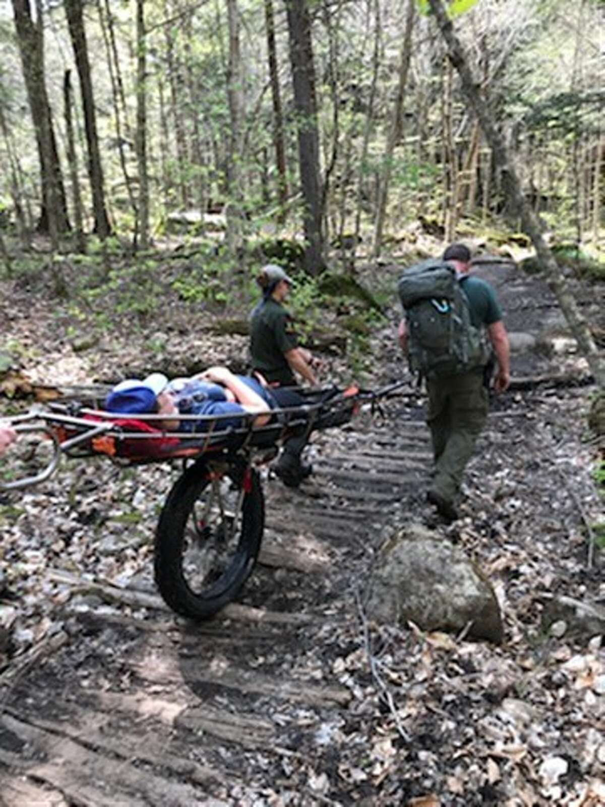 An injured hiker is taken off of Ampersand Mountain in the Adirondacks in a wheeled litter.