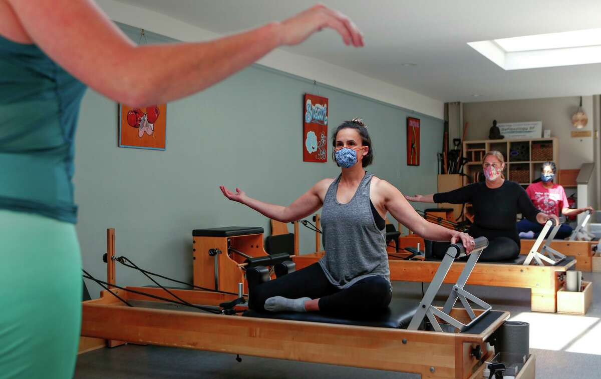 Danielle Kellar (center) and Penelope Robinson follow instructor Myra Phipps (left) in May at EHS Pilates Studio in S.F.