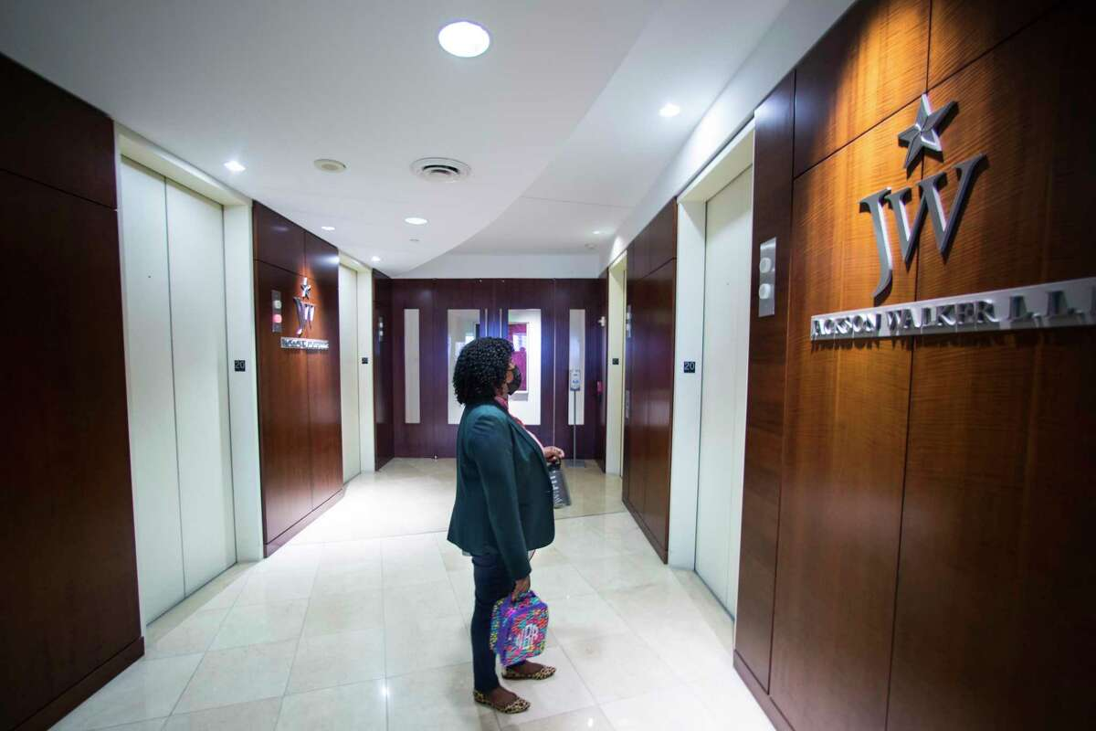 Labor and employment attorney Jamila Brinson, waits for an elevator office as she leaves for the day at the Jackson Walker law firm, where she is a partner, Thursday, May 20, 2021 in Houston. Jackson Walker brought employees back to their Downtown office for the first time this week, days after the Centers for Disease Control and White House announced new guidelines for mask-wearing and social-distancing for vaccinated people.