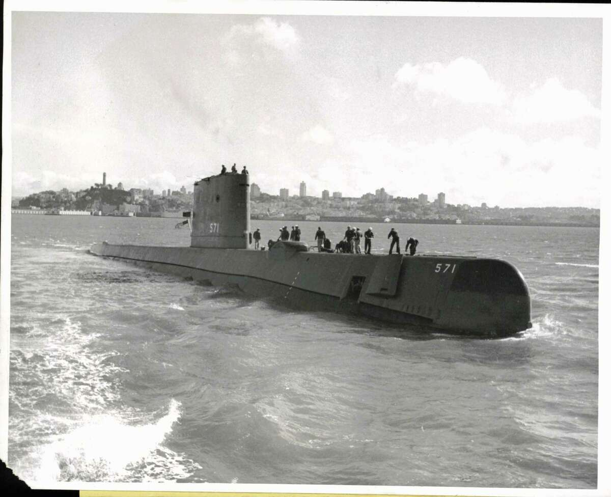Ships - Nautilus, U.S.S. (submarine). Takes off - San Francisco: Officers and men are on the forward deck of the USS Nautilus, Navy's first nuclear-powered submarine, as she prepares to depart the San Francisco Bay Area here after giving a demonstration to the press and VIPs. In background is the San Francisco skyline.