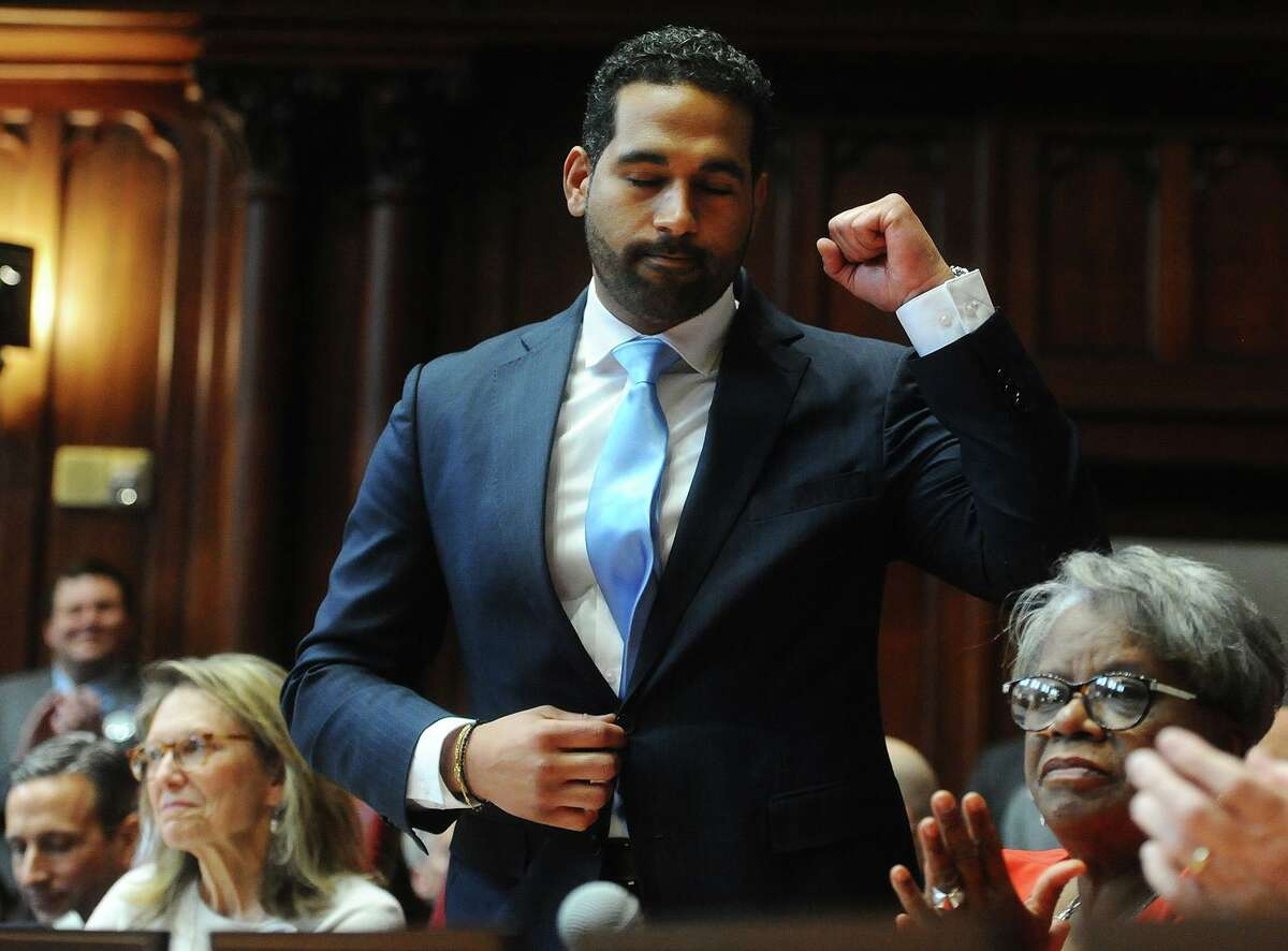 State Senator Dennis Bradley, D-Bridgeport, pumps a fist after being introduced during the opening session of the senate at the Capitol in Hartford, Conn. on Wednesday, January 9, 2019.