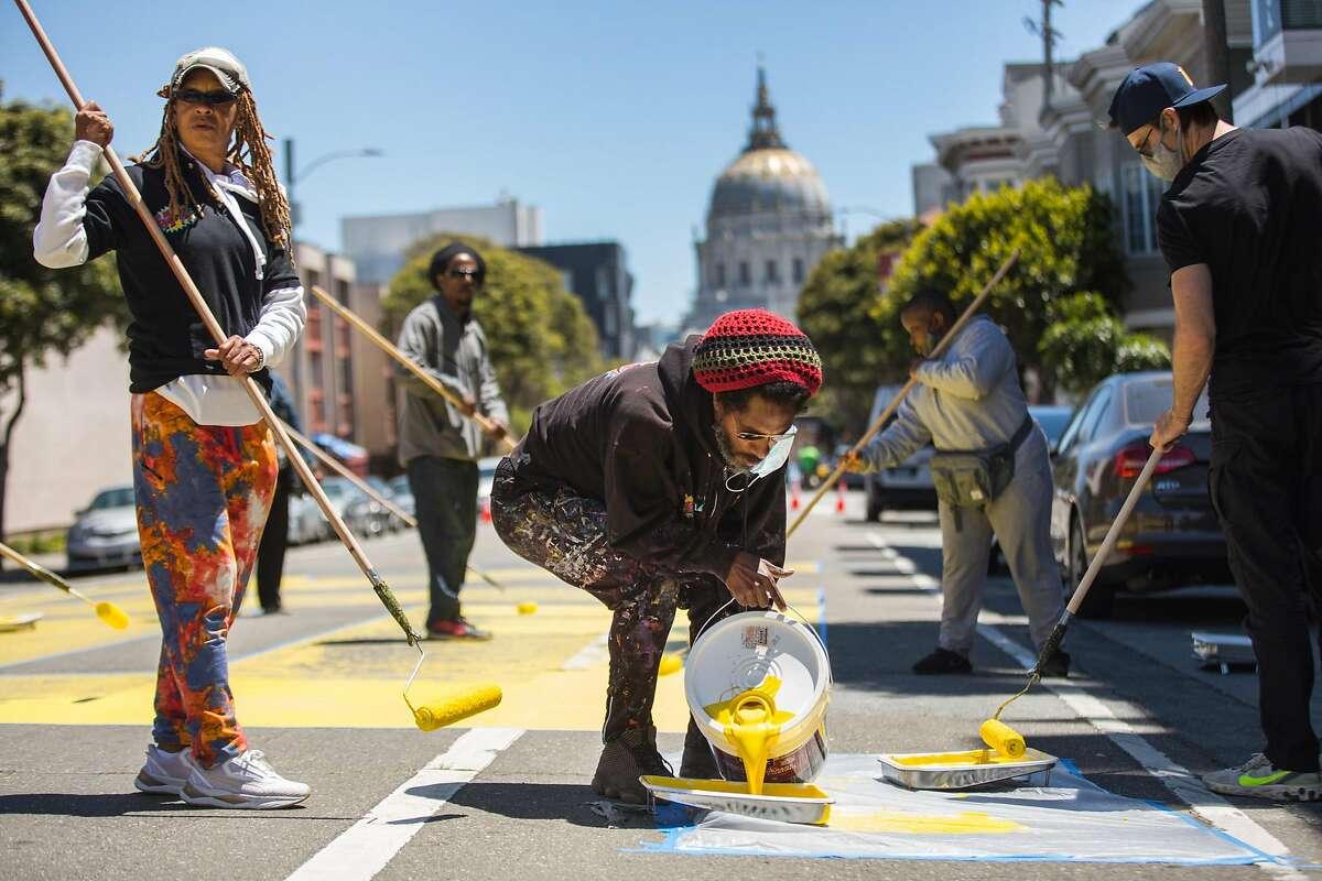 "Andre Jonesof Bay Area Mural Program helps with repainting of ""Black Lives Matter"" on Fulton Street."