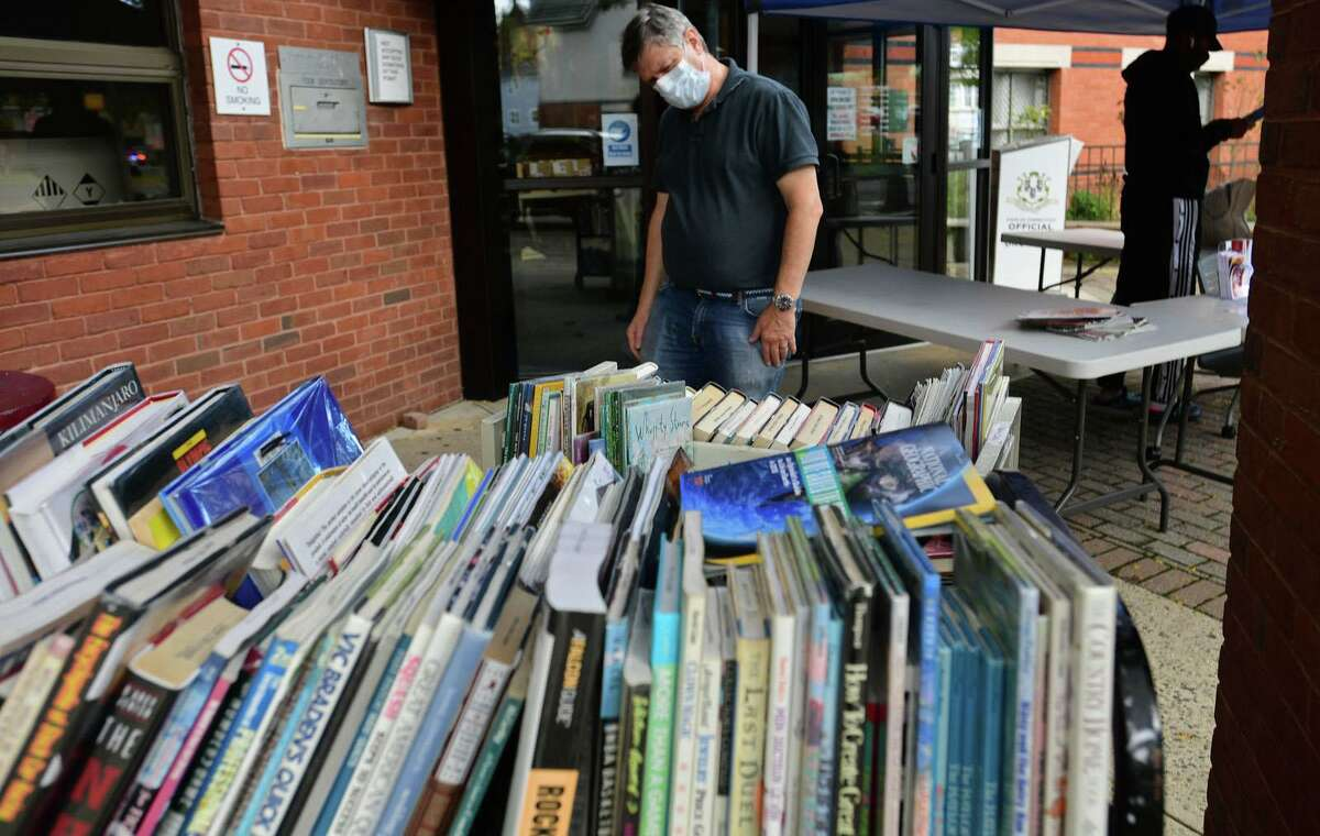 Norwalk Public Library patron Perry Fryman peruses the book selection at books during the sidewalk service option offered weekdays at the main branch Wednesday, September 30, 2020, in Norwalk, Conn.