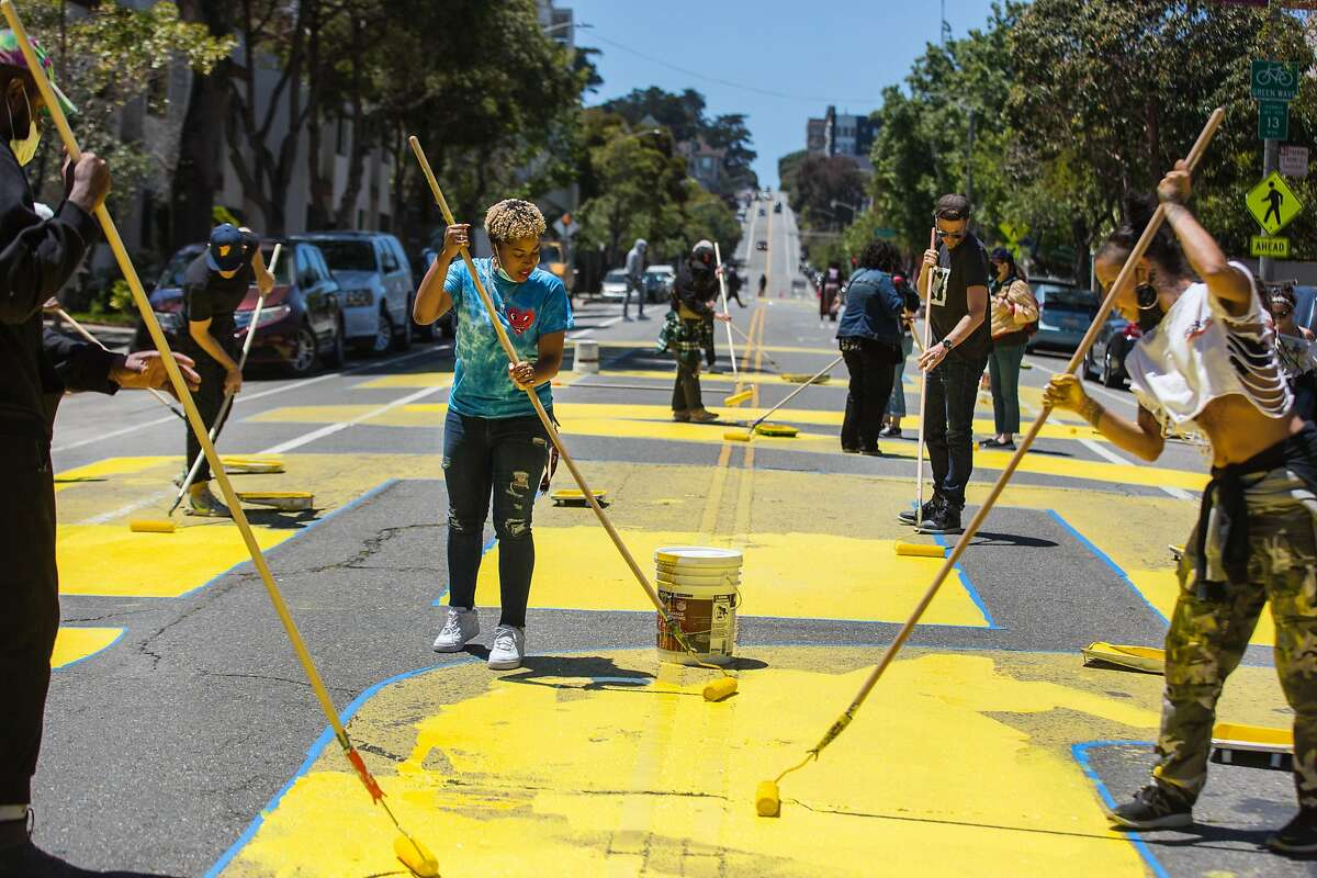 """On the anniversary of the killing of George Floyd in Minneapolis, activists on Tuesday repaint """"Black Lives Matter"""" on San Francisco street."""