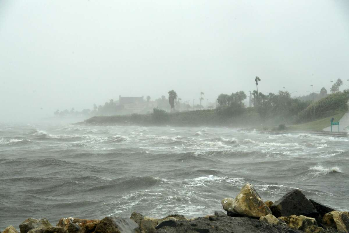 TOPSHOT - Strong winds batter seaside houses before the approaching Hurricane Harvey in Corpus Christi, Texas on August 25, 2017. Hurricane Harvey will soon hit the Texas coast with forecasters saying it's possible for up to 3 feet of rain and 125 mph winds. / AFP PHOTO / MARK RALSTON (Photo credit should read MARK RALSTON/AFP via Getty Images)