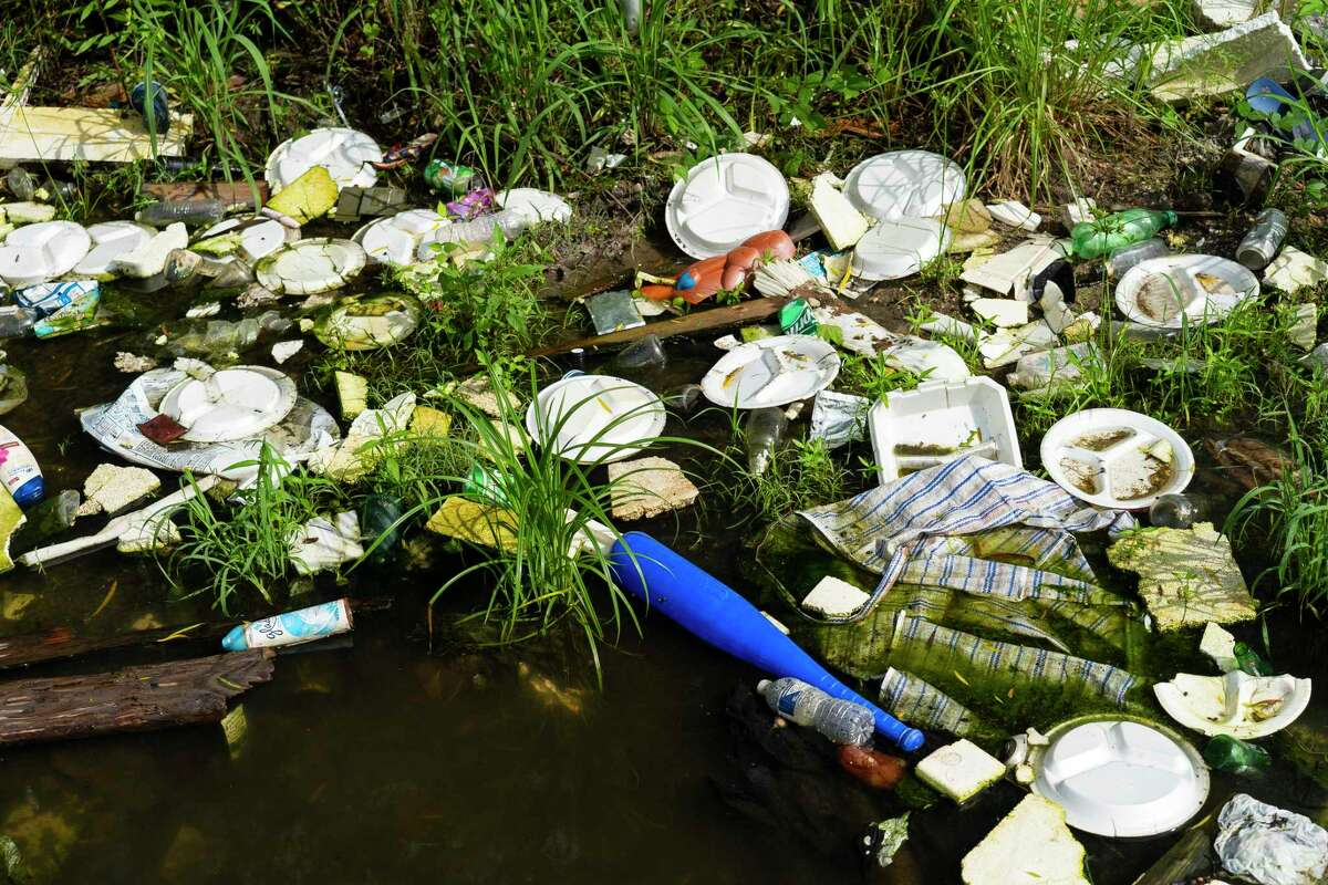 Garbage fills a ditch at an illegal dumping site in Fifth Ward, Tuesday, May 25, 2021, in Houston.