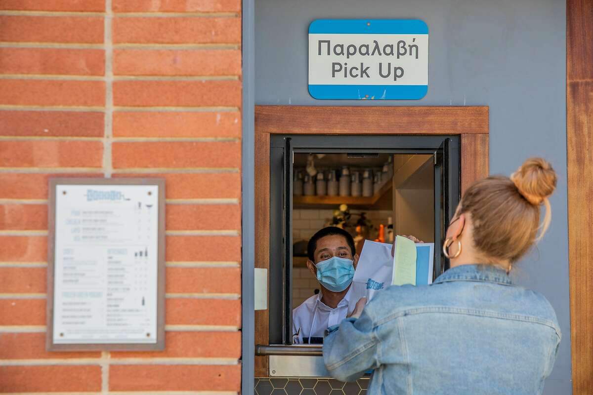 Ashley McCaffrey picks up her food order from Robert Anies at the pickup window at Souvla in S.F.