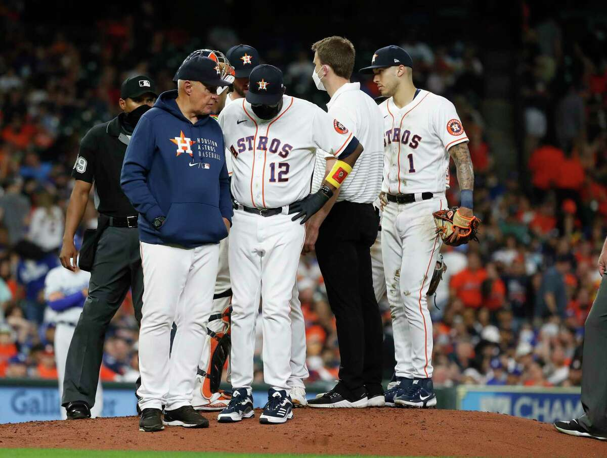 Houston Astros pitching coach Brent Strom (56) and Houston Astros manager Dusty Baker Jr. (12) discuss an issue with relief pitcher Kent Emanuel who was taken out of the game after just a few pitches during the eighth inning of an MLB baseball game at Minute Maid Park, Tuesday, May 25, 2021, in Houston.