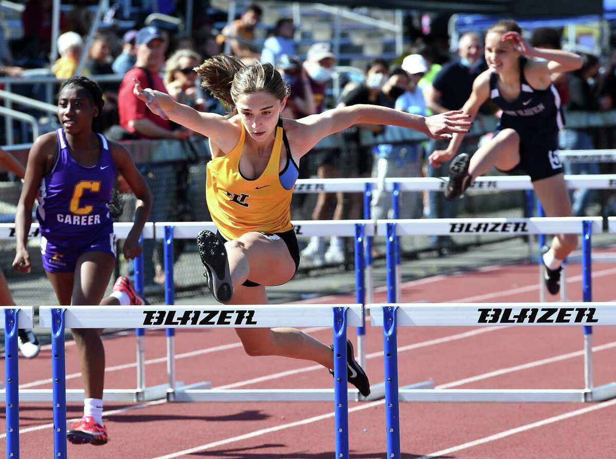 Law's Caden Simpson clears the last hurdle to finish first in the 100 meter hurdles at the SCC outdoor track and field championship on Tuesday at Bowen Field in New Haven.
