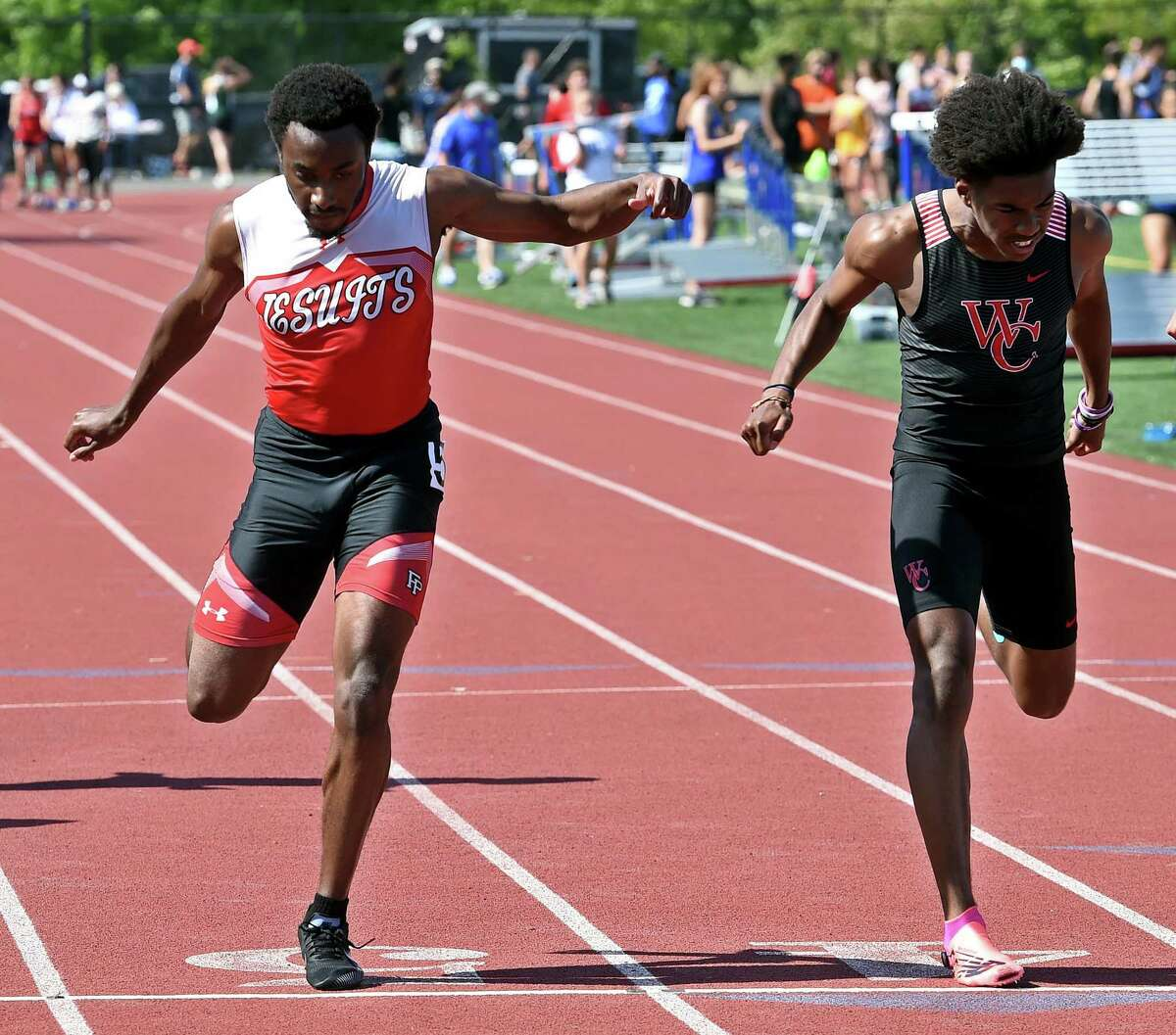 Fairfield Prep's Darren Blount, left, finishes second and Wilbur Cross' Devin Cue finishes third in the boys 100 meter dash finals at the SCC outdoor track and field championship on Tuesday at Bowen Field in New Haven.